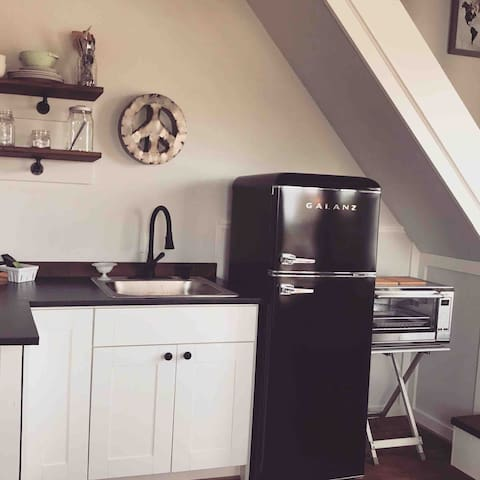 Kitchenette equipped with toaster oven, small retro fridge and coffee pot.