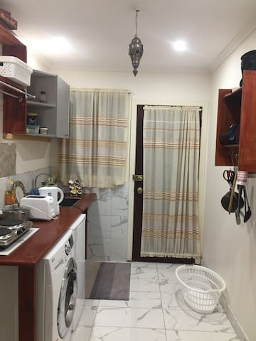 The kitchen/laundry are next to your bathroom and bedroom, so you do not have to move much. This area is totally independent, has a washing machine, small fridge, electric cooktop, first aid box, utensils, tea, coffee and other necessities.
