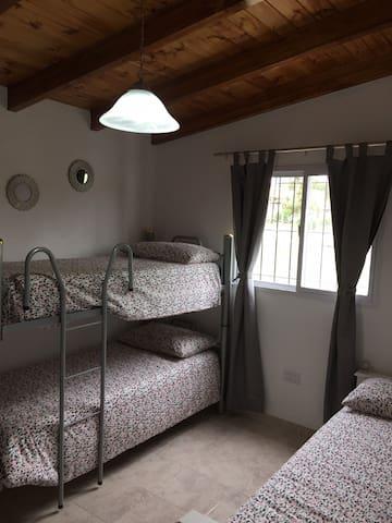Habitacion con cama cucheta y cama marinera donde duermen 4 personas. Ventilador de pared, placard amplio.