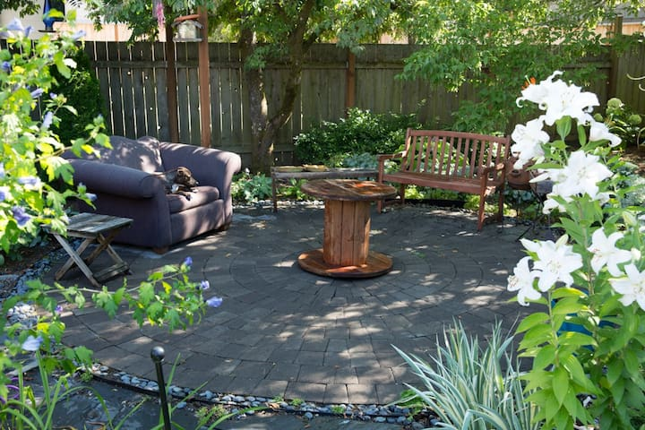 Seating area in the backyard offers plenty of space for a small group. If you ask nicely, the dog might even allow you to sit in that overstuffed chair!
