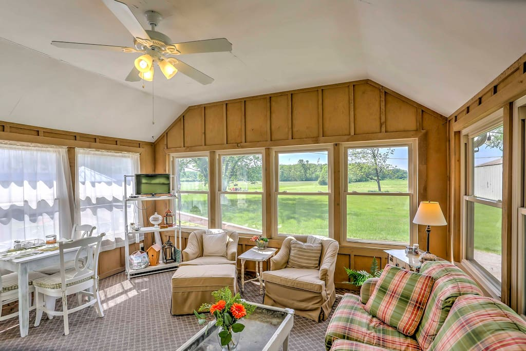 The welcoming sun room boasts comfortable furnishings, a flat-screen TV and natural light flooding from wall-to-wall windows.