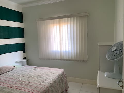 cama de casal confortável, ventilador e cómoda para guardar roupas