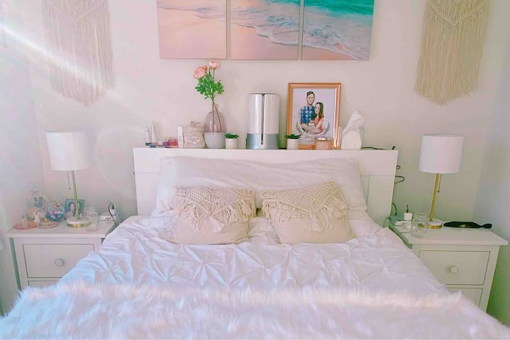 Our Fluffy-Cloud-Themed Bedroom is the ideal place for relaxation, featuring a queen-sized bed with high-quality mattress and pillows, bed board with side storage, Honeywell humidifier, charging consoles, and matching nightstands and table lamps.