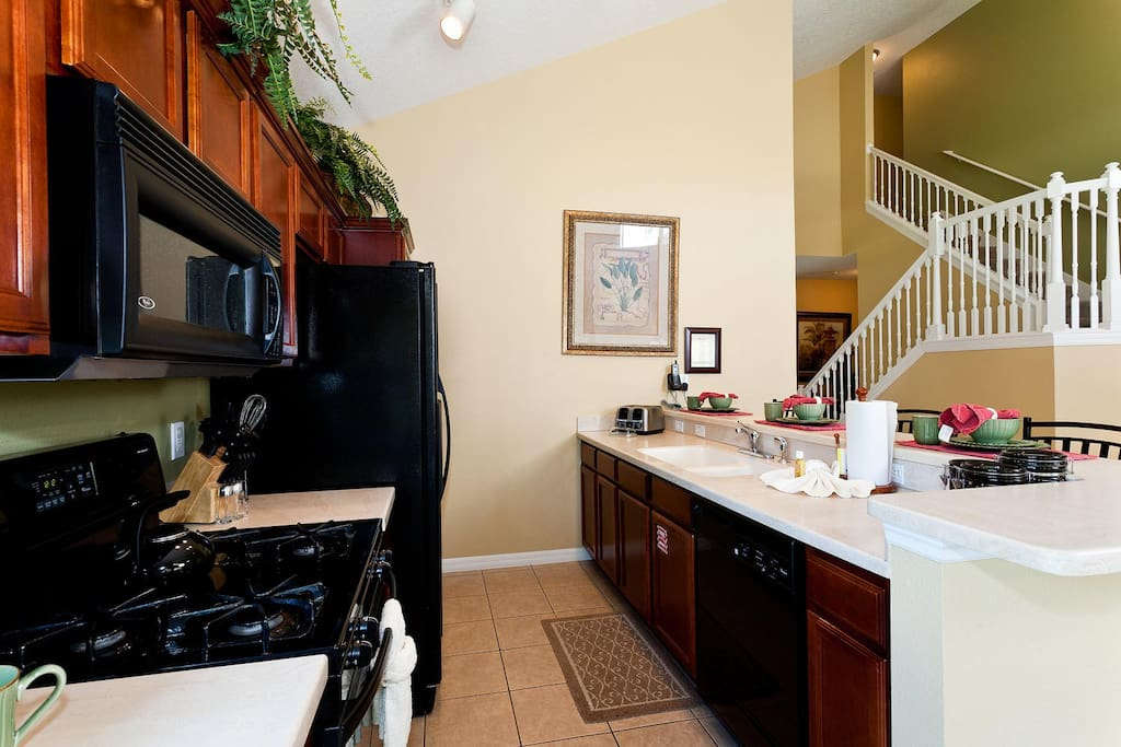 Fully equipped eat-in kitchen with custom cabinetry & Corian countertops