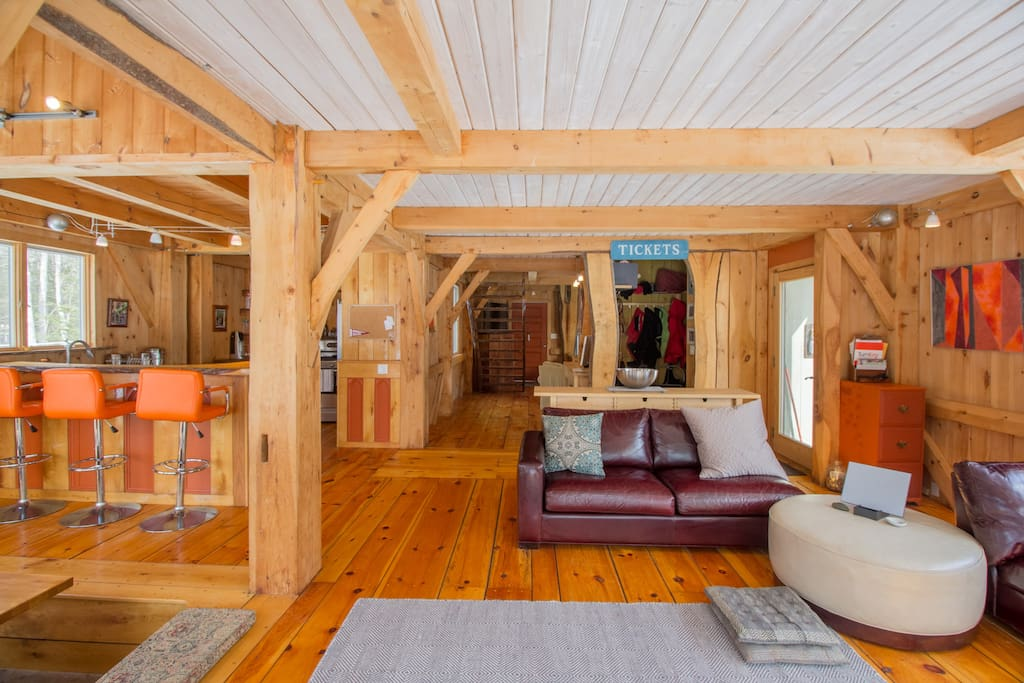 The living room has wide-plank wood floors and cozy couch