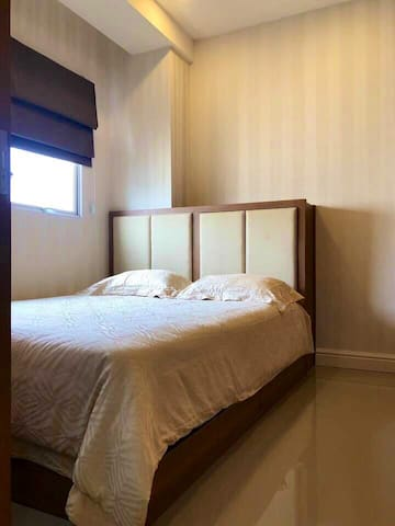 This is the master bedroom with a queen-sized bed. It has a facing window overlooking the city from 15th floor and it has a large closet with space enough for your clothes. The room has sliding door access and Air Conditioner to keep your room cool and comfortable.