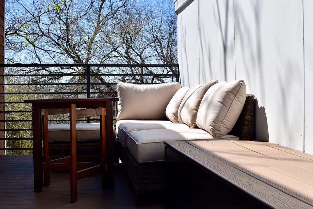 Roof top deck with comfy couch and table on one end, and two lounge chairs on the other end. Direct access from the loft bedroom.