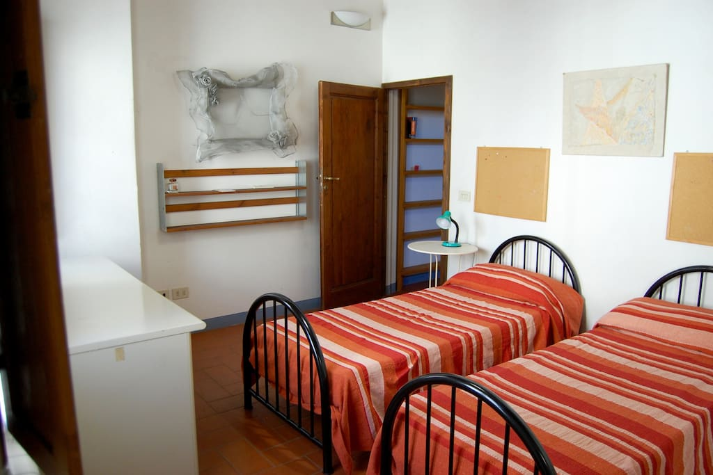 Bedroom with two twin beds, a desk, large wardrobe, en suite bathroom and two windows