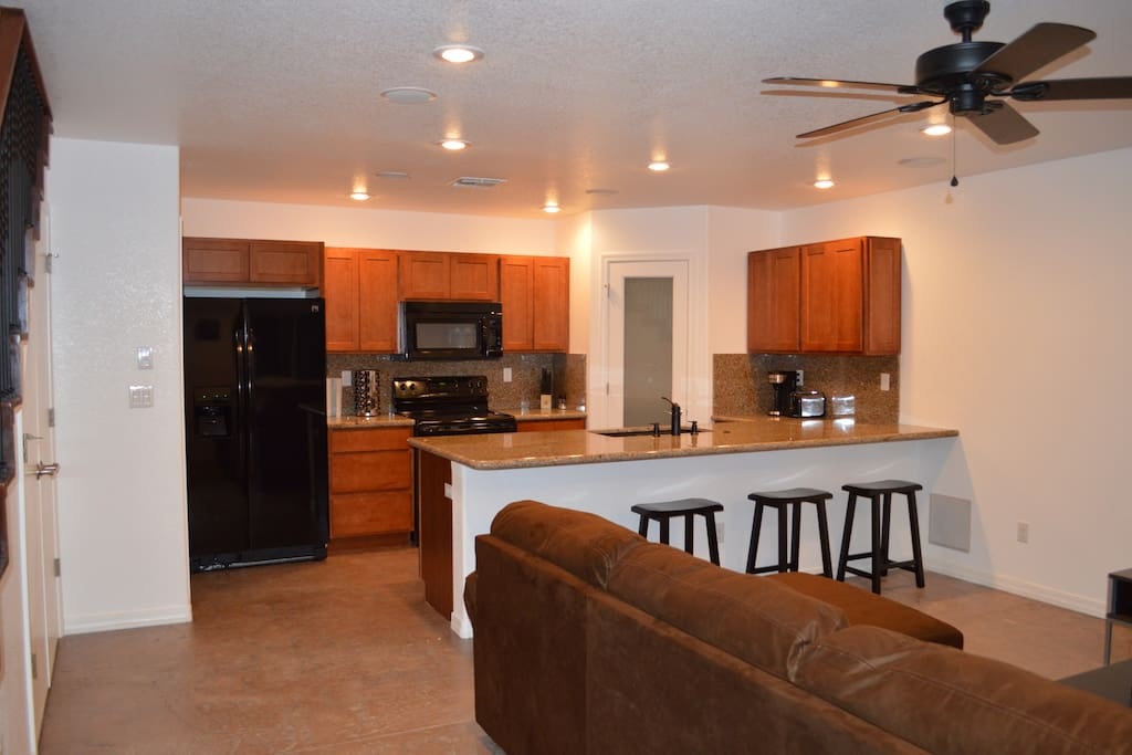 Gourmet kitchen with pantry, granite counters, and bar counter with stools, laundry room located under the stairs and large comfortable couch.
