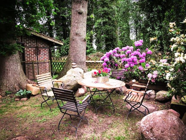 Gemütliche Sitzgruppe zwischen Eichen und Rhododendron
