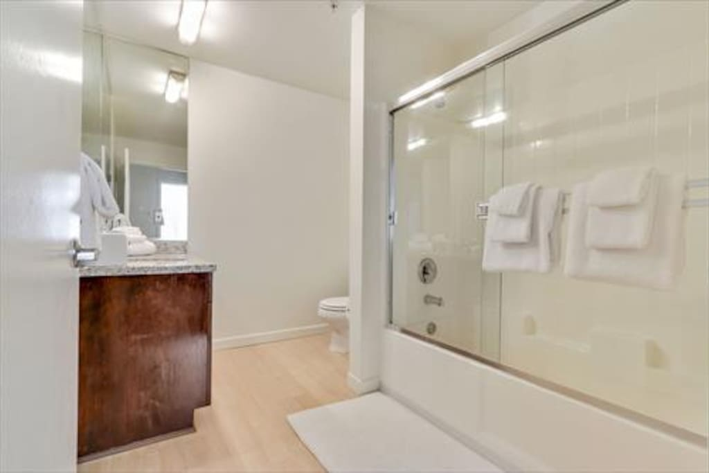 Large bathroom with shower/tub combination; towels & toiletry samples provided