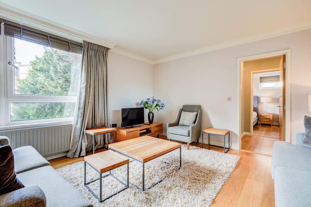 Very large living room with dining table, sofas, TV