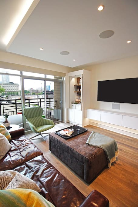 """Living room with comfortable seating, 65"""" 4K LG OLED television, and Dolby atmos surround sound."""