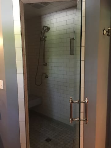 Large shower with beautiful tiles and seat. Hand held shower head and plenty of space.