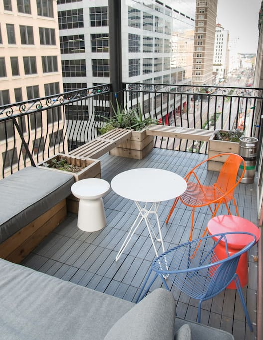 Large balcony on Main Street features custom made day bed, seating and planters