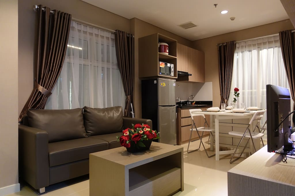 Living Area equipped with comfortable sofa, TV, Air Conditioning and Coffee Table.