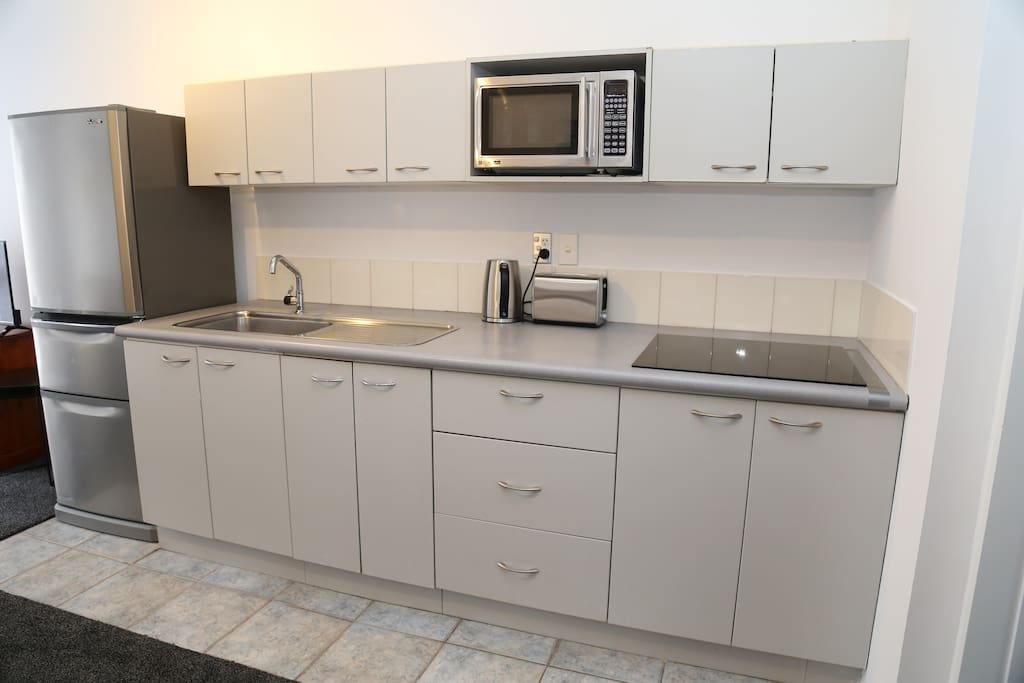 Kitchenette with microwave and full fridge, plates and cutlery etc.