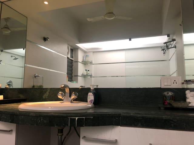 Clean and modern bathroom with a complimentary shower kit and fresh towels.