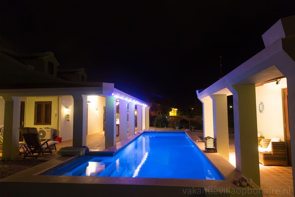 Verlicht zwembad in de avond. Een ideale plek om de sterrenhemel te bekijken! Zwembad met inlooptrap, 10 x 3 meter. Voorzien van verlichting en buitendouche. Diepte: 1,75 meter.
