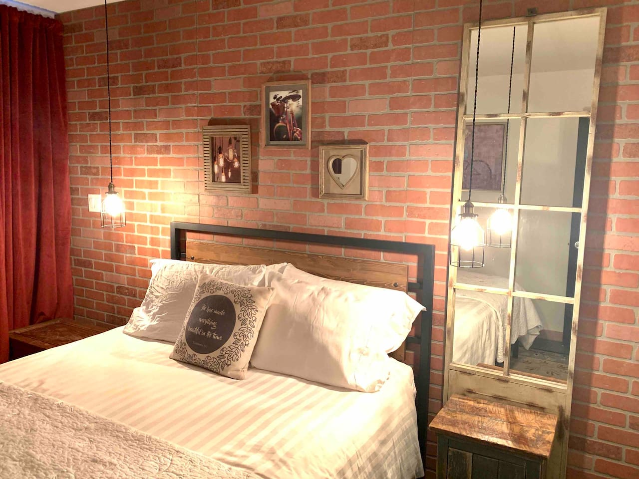 Adventure Room with comfortable queen bed and quality linens. Beautiful brick decor as a backdrop for industrial furnishings