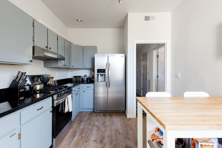 Enormous shared kitchen, fully stocked with modern appliances.