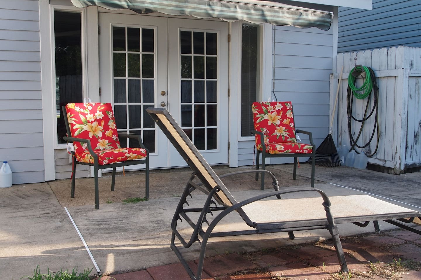 Patio with sun setter awning fenced backyard