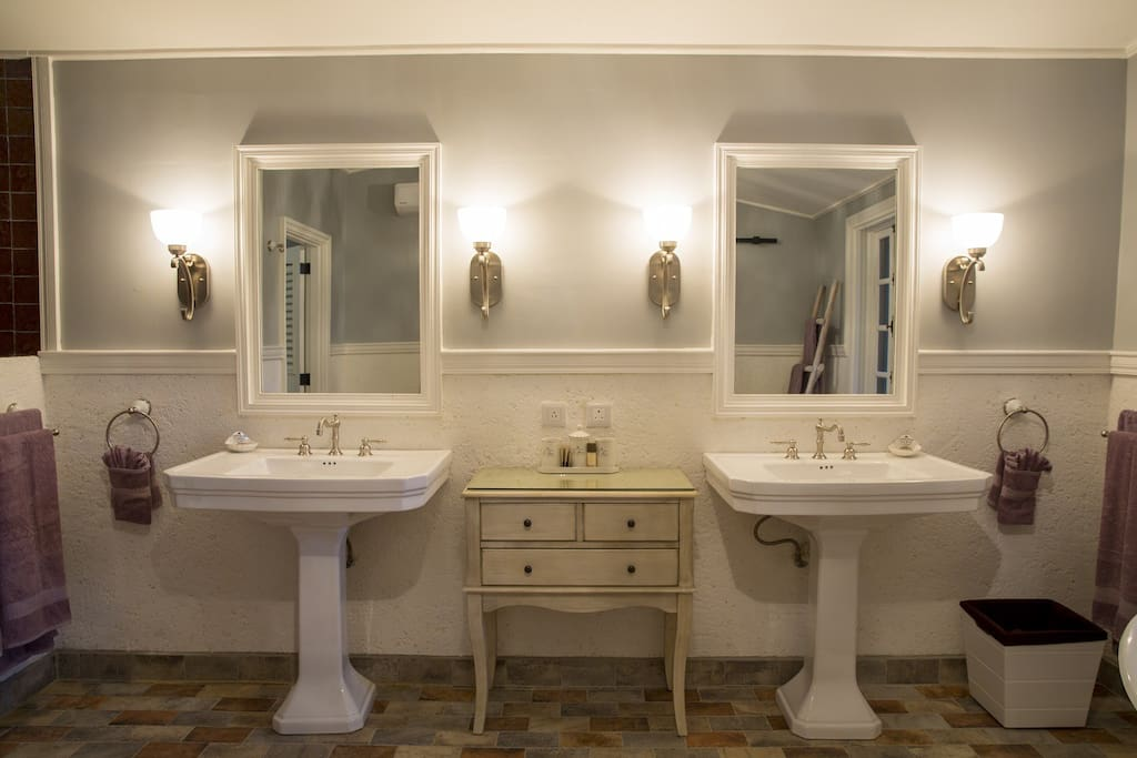 Two large, rectangular white porcelain pedestal sinks with inset mirrors and glass wall sconces immediately capture your attention