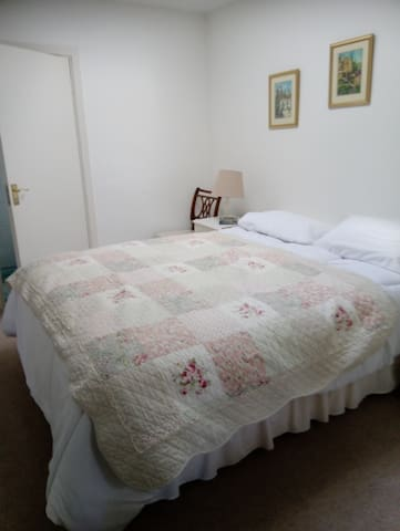 Spacious bedroom with king size bed and en - suite bathroom and double built in wardrobes.