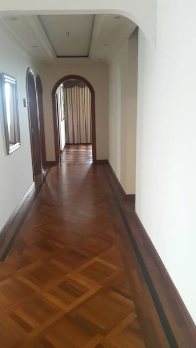 Luxurious walkway with real wooden tiles to bedroom with ensuite bathroom