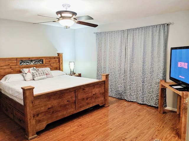 """Master bedroom w/ king bed 50"""" TV, Chromecast and attached bathroom."""