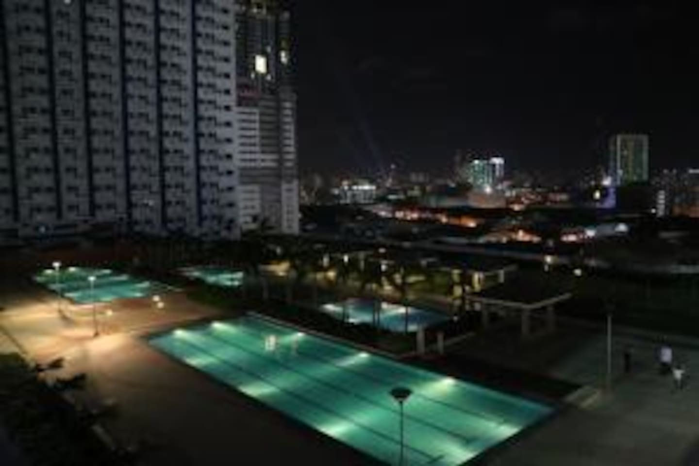 View of the pool and garden area at night. Good for staycationer.