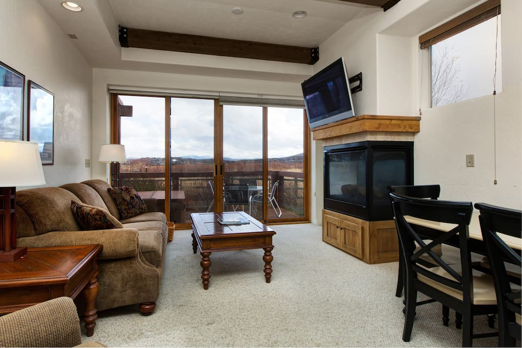 Mountain-view living area with a flatscreen TV and gas fireplace.