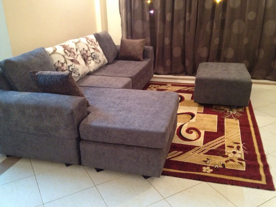 More view of the sitting area carpeted , puff to rest your feet as you watch tv.or look through the glass sliding doors facing Mombasa road.