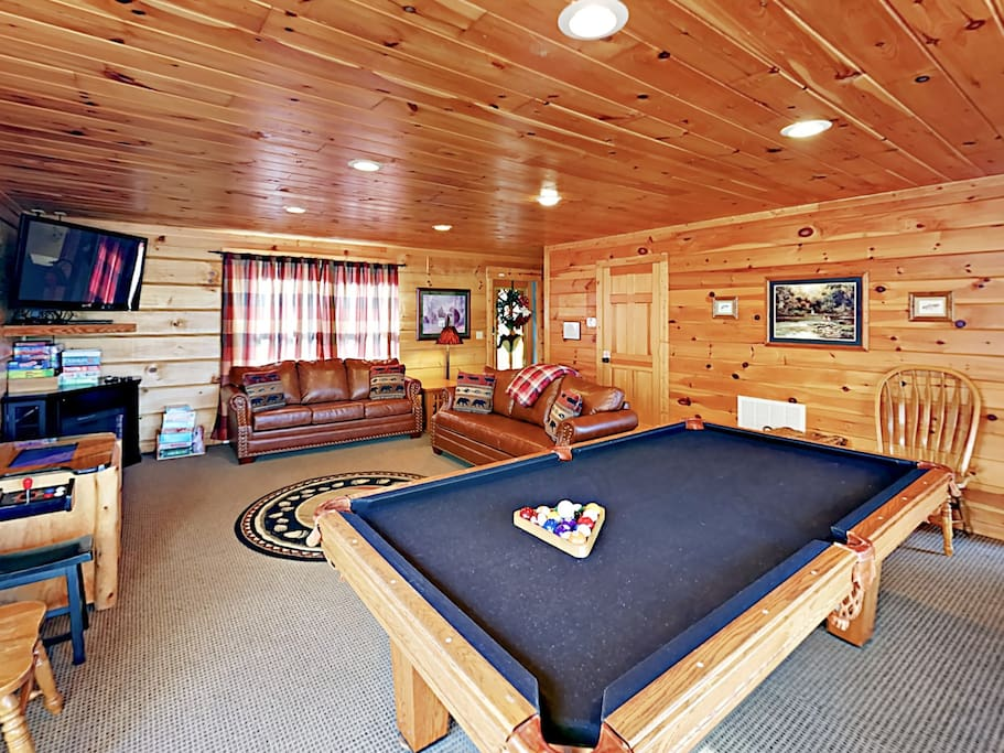 Game room with a convertible pool and ping pong table, an arcade system, and a wide selection of board games.