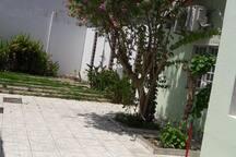 Área aberta com jardins e ducha ao fundo