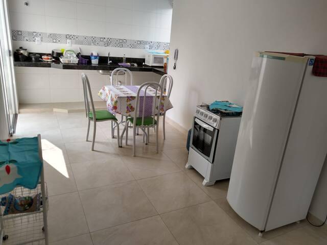 Cozinha c/ mesa, cadeiras, fogão, geladeira e microondas.