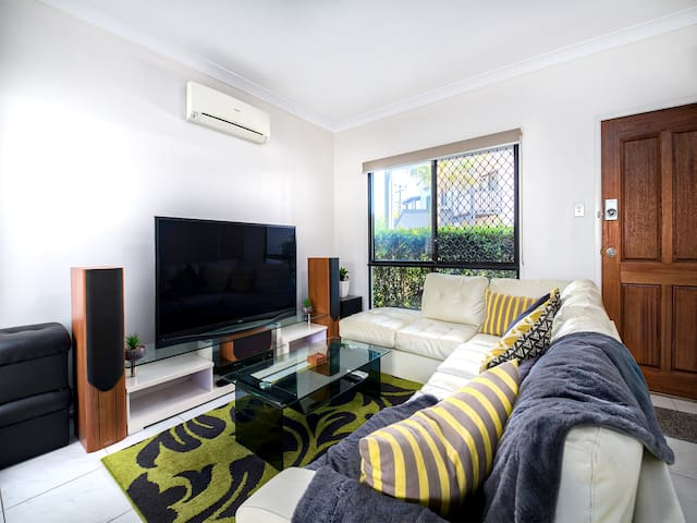 """My comfortable living room with huge corner couch, 65"""" Samsung flat-screen TV with Netflix, high quality surround sound and Chromecast"""