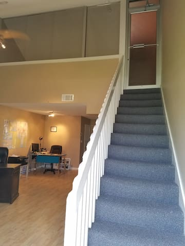 Stairs as you come in from the front door to your private unit. Our office is on the left.  The entire place upstairs has the beds, and private bathroom.  Unit door has a key so you can lock it up.