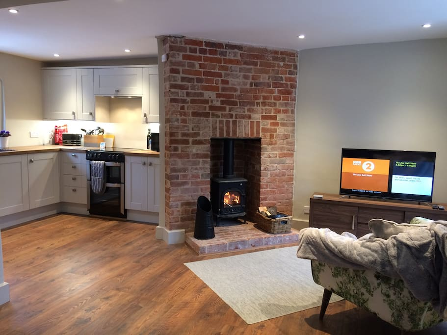 "A welcoming stove gives a cosy feel to the open plan lounge dining area.  Smart 40"" TV DVDs & traditional board games & DVDs"