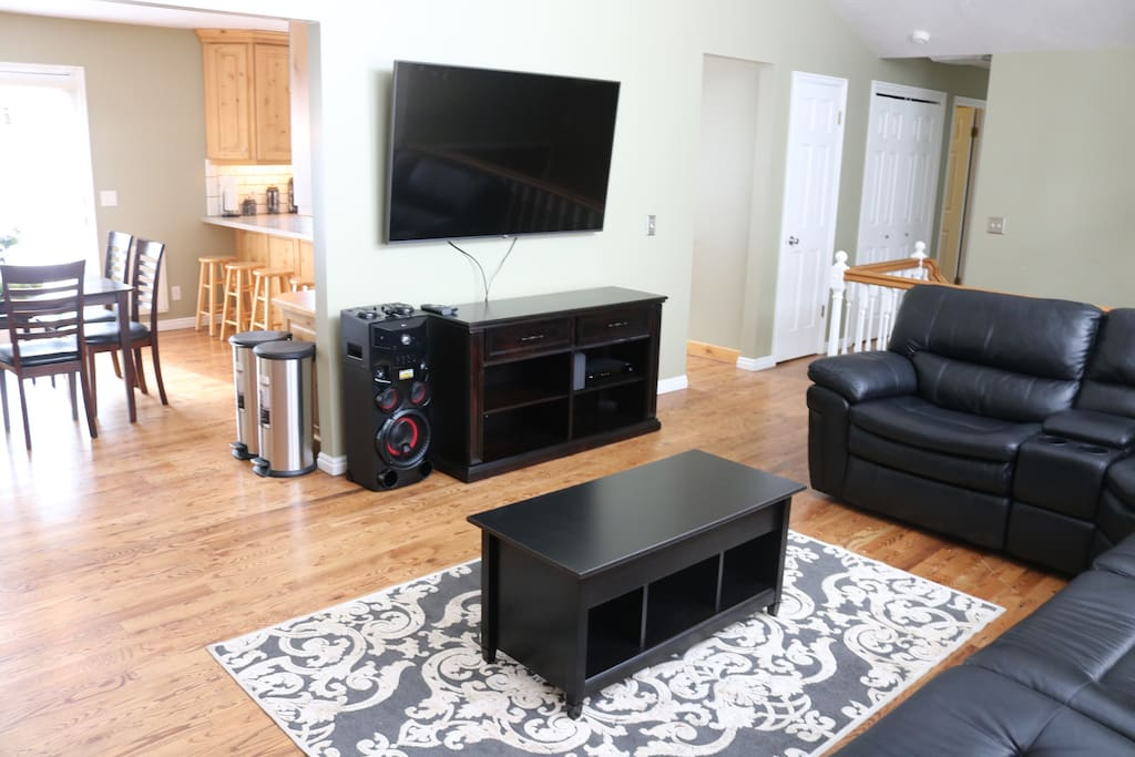 """Listen to music, watch your favorite show on a 65"""" TV with Xfinity and lounge on this comfy leather couch big enough for a large group of people."""