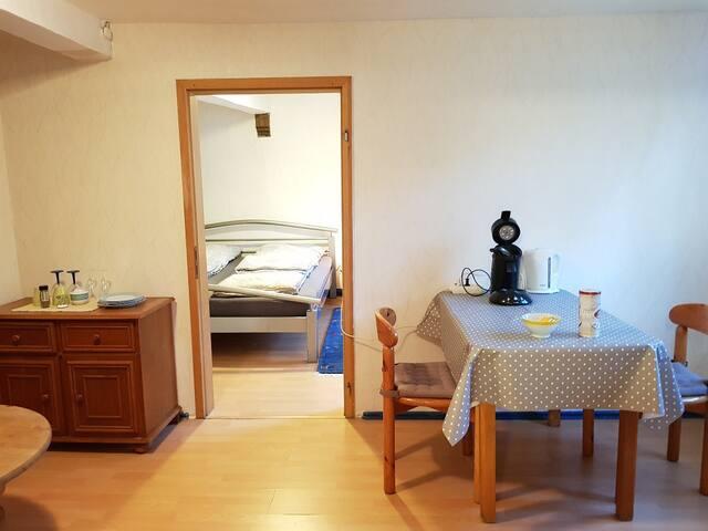 Anliegender Raum mit Frühstücksecke, Blick ins Schlafzimmer