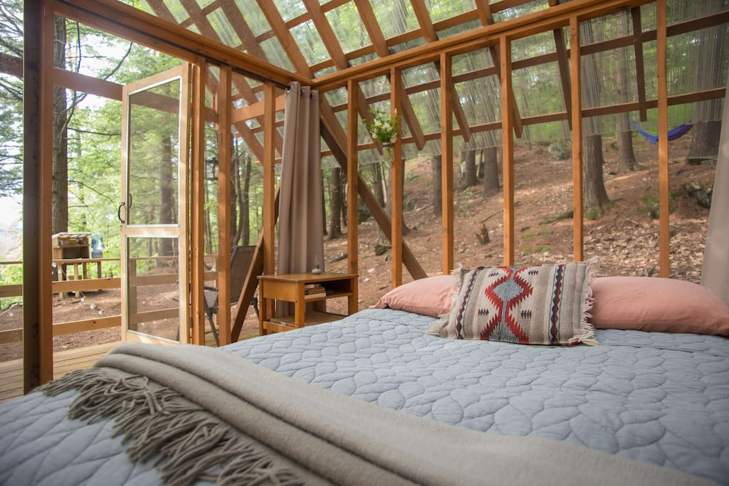 A cozy bed in the forest - protected by screened walls - lets you enjoy the feeling of being surrounded by nature.