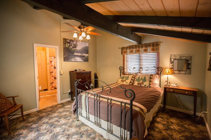 upper level bedroom with queen sized bed and en suite bath, there is an a/c unit for the summer months