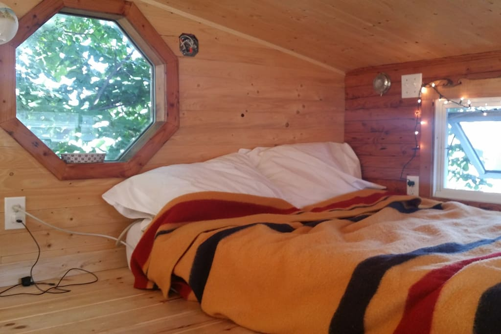 The sleeping loft has lots of headroom, as tiny houses go, and an outlet nearby to charge your devices.