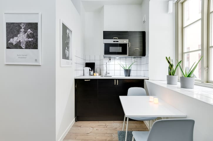 """Small """"kitchen"""" with micro, fridge and dishwasher. Kettle and one stove top."""