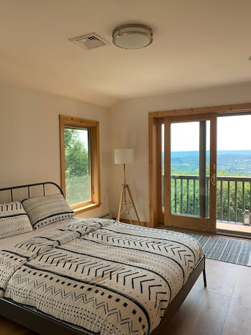 Second bedroom with small balcony and queen bed.