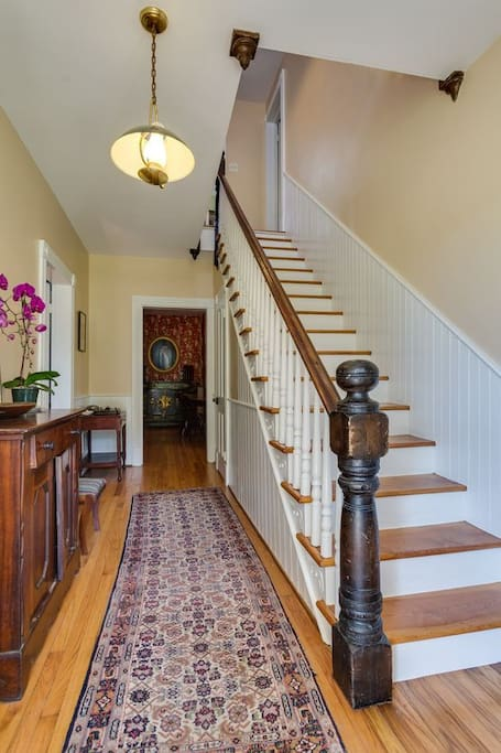 Inviting foyer with hardwood floors and wainscoting