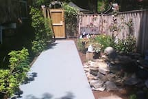 Side yard with pond and vegetable garden. Outdoor shower recently added