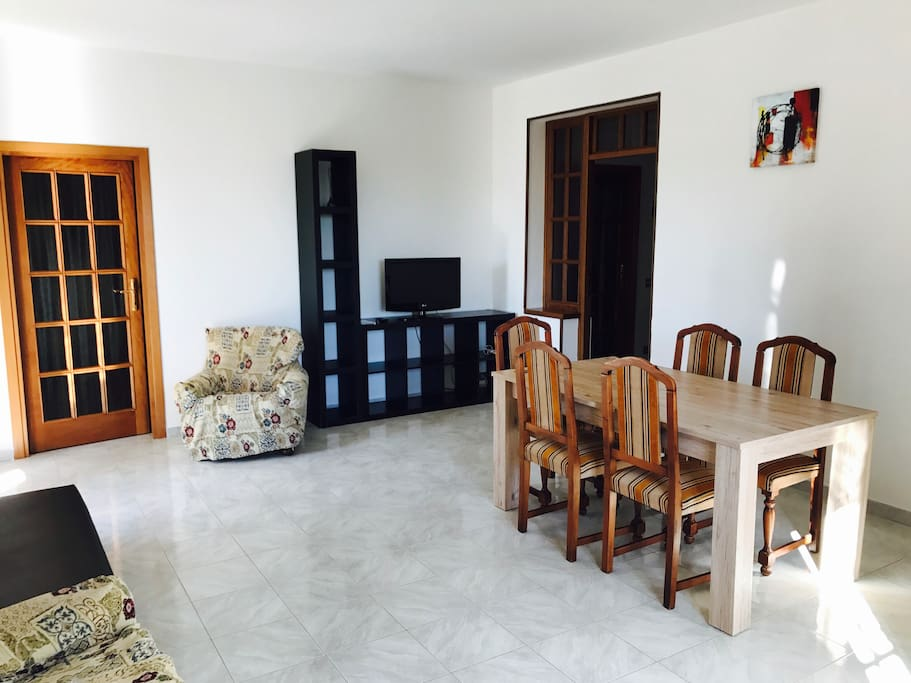 Living room: - TV; - Table; - 2 armchairs, - 1 sofà; - kitchen corner; - 45 squared meters of available space; - 2 windows with view in the garden;