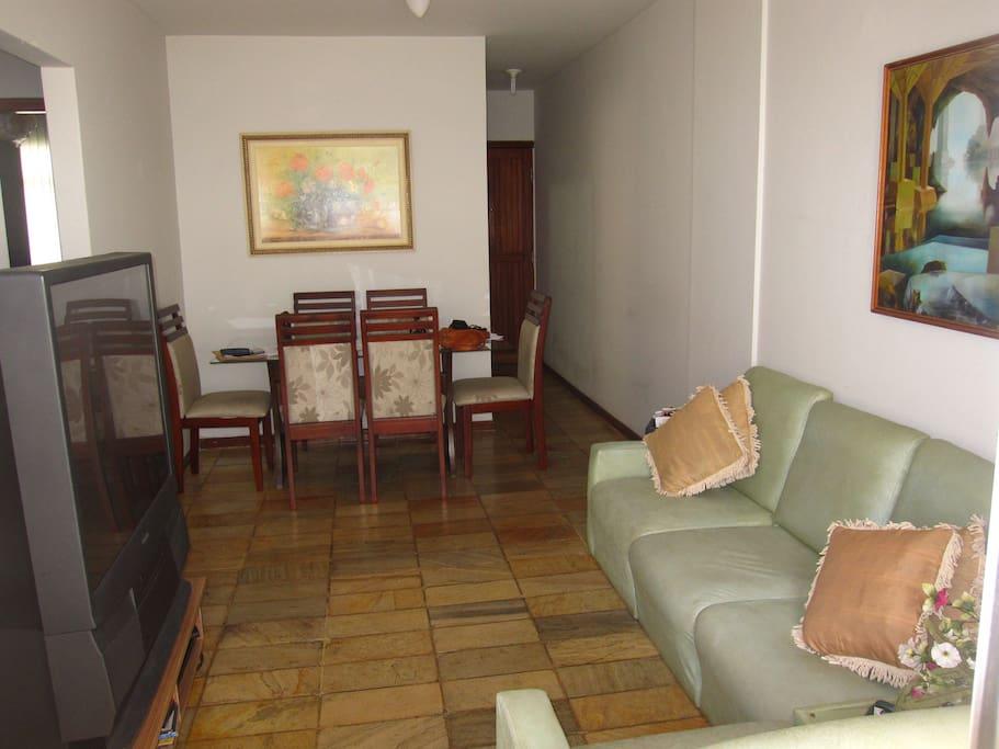 Vista da sala com Tv, sofa e mesa de jantar.